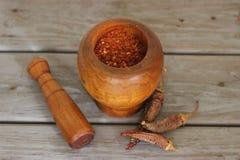 Torkade röda peppar och krossade röda peppar i en mortel Arkivfoto