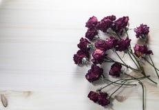 Torkade rosor på en trätabell Ställe för din text royaltyfria foton