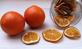 Torkade skivor av apelsiner och nya apelsiner på en tabell Arkivfoto