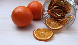 Torkade skivor av apelsiner och nya apelsiner på en tabell Royaltyfria Bilder