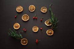 Torkade skivor av apelsiner på mörk brunt svärtar bakgrund med rött arkivfoto