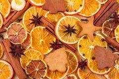Torkade skivor av apelsiner, stjärnaanis, kanelbruna pinnar och pepparkakor på beige bakgrund, julbakgrund Royaltyfri Bild