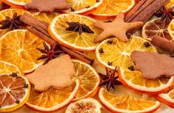 Torkade skivor av apelsiner, stjärnaanis, kanelbruna pinnar och pepparkakor på beige bakgrund, julbakgrund Fotografering för Bildbyråer