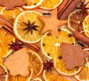 Torkade skivor av apelsiner, stjärnaanis, kanelbruna pinnar och pepparkakor på beige bakgrund, julbakgrund Royaltyfria Foton