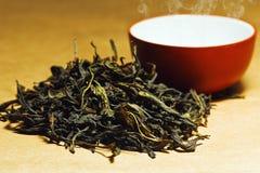 Torkade teblad nära koppen för traditionell kines Arkivfoto