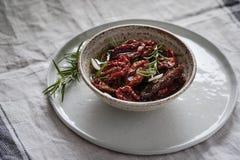 Torkade tomater i en bunke med ny kryddor och olivolja Arkivfoto