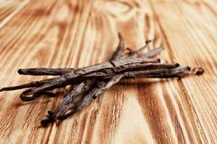 Torkade vaniljpinnar på träbakgrund royaltyfri bild