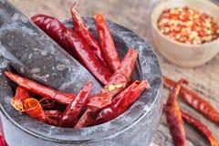 Torkade varma peppar i mortel och mortelstöt Arkivfoton