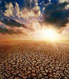 Torkajord och solnedgång Arkivbilder