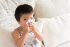 Torkande eller rengörande näsa för sjuk liten asiatisk flicka med silkespappret royaltyfri foto
