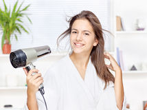 Torkande hår för kvinna hemma Royaltyfri Foto