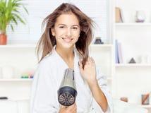 Torkande hår för kvinna hemma Royaltyfria Bilder