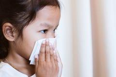 Torkande och rengörande näsa för sjuk asiatisk barnflicka med silkespappret arkivfoton