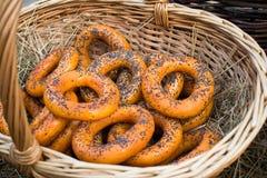 Torkar, baglar, guld- bakade och för sötsak runda bullar med vallmo i form av cirklar i vide- korgar som göras från en vinranka a Royaltyfria Foton
