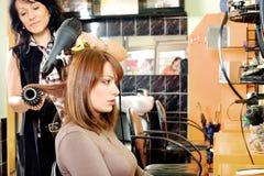 Torkar hår i en hårsalong Arkivbild