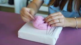 Torkar unga caucasian kvinnahänder för closeupen som gör ull, orubblig felting stock video