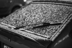 Torkare och vindruta av den parkerade bilen som täckas med snö Arkivbild