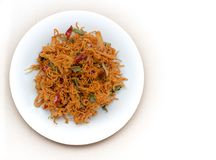 Torkat fegt kött med chilipeppar och kryddor med lagerbladar på en platta på vit bakgrund royaltyfri bild