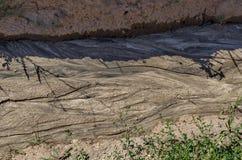 Torkat land med teckningen efter flodregn i fältet Royaltyfria Bilder
