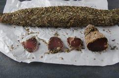 Torkat stycke av kött och skivor av det på vitbok arkivfoto