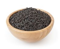 Torkat svart te i träbunken som isoleras på vit bakgrund Arkivfoto