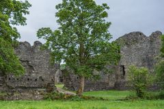 Breach in wall of Inverlochy Castle, Scotland. Torlundy, Scotland - June 11, 2012: Outside wall with breach of Invelochy Castle under gray skies. Green trees royalty free stock photography