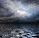 Torm sky over water surface. Dark storm sky over water surface with artistick shadows added Royalty Free Stock Images