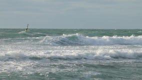 Tormenta con el windsurfer en el agua Ondas potentes enormes que se rompen en el malecón en tormenta severa importante almacen de video