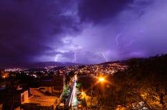 Tormenta de la iluminación sobre una ciudad en la noche fotos de archivo libres de regalías