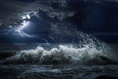 Tormenta oscura del océano con lgihting y ondas en la noche