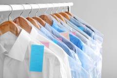 Tormenti con i vestiti puliti sui ganci dopo avere pulito a secco fotografia stock