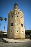 Torn av guld i Seville med palmträd på klar dag Royaltyfri Bild