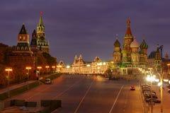 Torn av MoskvaKreml och St Basil Cathedral på röd fyrkant med nattbelysning mot mörkt - blå himmel royaltyfri foto