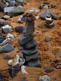 Torn av strandkiselstenar som är upprätta på sand arkivfoto