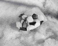 Torn ball for playing soccer lying on the snow royalty free stock photo