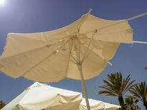 Torn beach umbrella lit by the sun against the sky. Travel Stock Images
