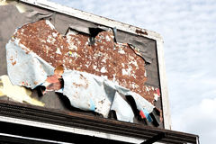 Torn Billboard. Weathered and torn advertising billboard against sky Royalty Free Stock Photography