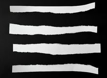 Torn blank white paper strips against a black background. Close up stock images