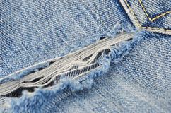 Torn blue jeans. Background, close up, DOF stock photos