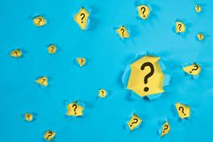 Torn blue paper revealing QUESTION MARK on yellow paper. Concept of questions, faq, q&a, problem, riddle and quiz background stock images