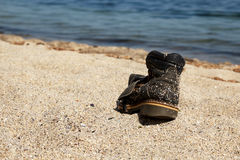 Torn boot on the beach. Old torn boot abandoned on the beach Stock Image
