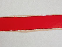 Torn cardboard over red paper background Royalty Free Stock Photo