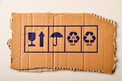 Torn cardboard and symbols Stock Photos