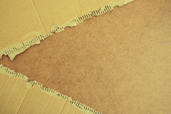 Torn cardboard texture on wooden background. Royalty Free Stock Photography