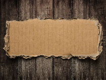 Torn cardboard on wood background Royalty Free Stock Photo