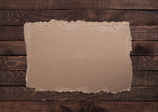 Torn cardboard on the wooden texture. Stock Photos