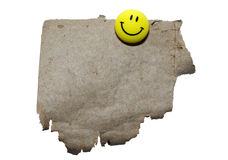 Torn cardboard with yellow smile. Royalty Free Stock Photos