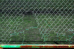 Torn chain link fence. Hole in mesh netting Royalty Free Stock Photo