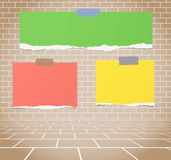 Torn colorful blank paper sheets stuck on brown brick wall Royalty Free Stock Photos