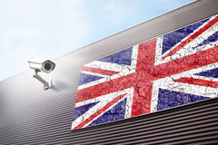 Torn cracked Uk flag and cctv. Conceptual cracked and torn United Kingdom flag and security camera on the new metal wall building Stock Image